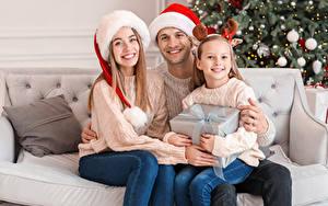 Обои Новый год Мама Мужчины Трое 3 Девочки Сидит Шапки Подарки Взгляд Семья Дети Девушки