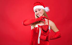 Фотографии Рождество Красный фон Блондинка Шапки Улыбка Перчатки Сердечко