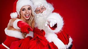 Обои Новый год Красном фоне Двое Очки Бородатые В шапке Радостный Санта-Клаус молодая женщина