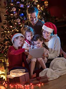 Картинка Рождество Планшет Мать Девочка Мальчишки В шапке Подарок ребёнок