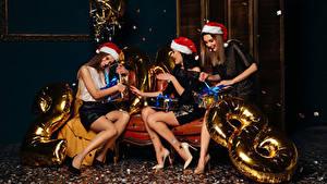 Картинки Рождество Втроем Шапки Подарки Радость Девушки