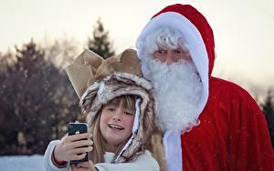 Картинка Рождество Зимние Дед Мороз Униформа Борода Девочки Вдвоем Селфи Смартфон Дети