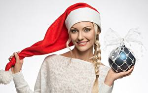 Обои Рождество Шапки Шар Коса Улыбка Серый фон девушка