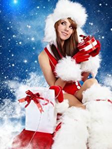 Фотографии Новый год Шапки Шатенка Сидящие Подарок молодая женщина