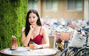 Картинки Кофе Азиаты Сидит Рука Милый Шатенки Смотрит Стола девушка