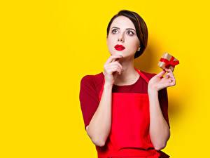 Фотографии Цветной фон Шатенки Красные губы Рука Подарок Смотрят молодые женщины