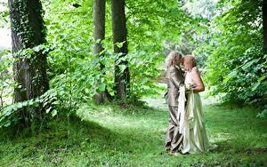 Фотографии Влюбленные пары Мужчины Женщины Трава Вдвоем Объятие Платье Свадьбы Жениха Невесты