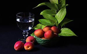 Фотографии Напитки Абрикос Черный фон Бокал Листва Миска Пища