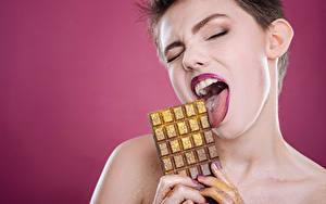 Картинки Шоколад Пальцы Шоколадка Цветной фон Шатенка Язык (анатомия) Девушки