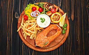 Фото Рыба Картофель фри Овощи Томаты Лимоны Лососи Разделочная доска