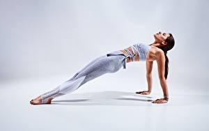 Картинка Фитнес Сером фоне Поза Руки Ноги Планка упражнение молодая женщина
