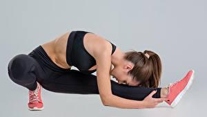 Фотография Фитнес Растяжка упражнение Ног Позирует Сером фоне Спорт Девушки