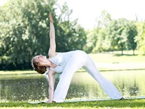 Картинки Фитнес Йога Трава Поза Шатенки Тренировка Рука Ног молодая женщина