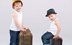 Картинки Серый фон Мальчишка Две Улыбается Шляпе Чемодан Дети