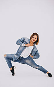 Картинка Сером фоне Шатенки Танцует Джинсов девушка