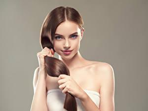Фото Серый фон Шатенки Волосы Руки Взгляд Красивый молодая женщина