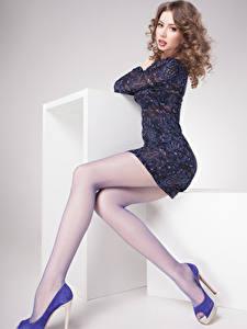 Картинка Серый фон Шатенка Сидящие Смотрит Платье Ноги Туфли