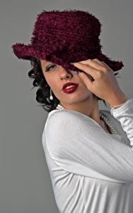 Фото Серый фон Брюнеток Позирует Взгляд Руки Шляпе Мейкап Девушки