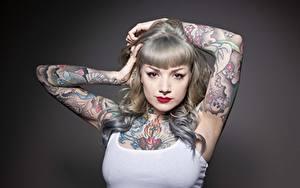 Обои для рабочего стола Сером фоне Смотрят Руки Татуировки Макияж Пирсингом молодая женщина