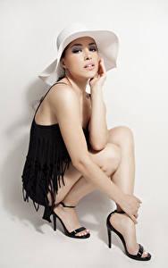 Картинки Сером фоне Шляпа Руки Ноги Сидя Туфли Поза молодая женщина