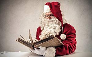 Фото Серый фон Санта-Клаус Книга Шапки Очки Борода Сидящие