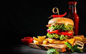 Картинки Гамбургер Картофель фри Овощи Черный фон Разделочная доска Бутылки Кетчуп Пища