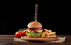 Фотография Гамбургер Помидоры Картофель фри Ножик На черном фоне Разделочной доске Пища