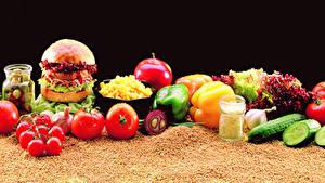 Фотографии Гамбургер Овощи Помидоры Огурцы Перец Черный фон Зерна Еда