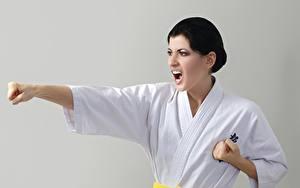 Картинки Сером фоне Руки Брюнетка Кричит Униформе Удар Karate Девушки