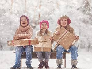 Фотографии Девочка Мальчики Сидит Подарок Счастливый Втроем Дети