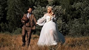Фотографии Мужчина Влюбленные пары Трава 2 Жених Невесты Блондинки Улыбается Платье Костюм