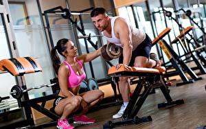 Фото Мужчины Спортзале Тренируется 2 Сидящие Гантеля спортивные Девушки