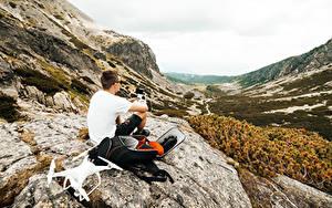 Фотографии Мужчины Горы Квадрокоптер Скала Сидит Рюкзак Природа