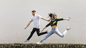 Картинка Мужчина 2 Прыгает Рука Шатенки Джинсов девушка