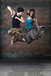 Картинки Мужчины Стенка 2 Танцует В прыжке Счастливые Рука Шапка Девушки