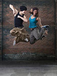 Картинки Мужчины Стенка 2 Танцует Прыжок Счастливые Руки Шапки Девушки