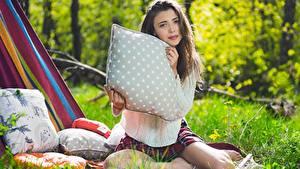 Обои для рабочего стола Mila Azul Шатенки Траве Подушка Смотрят Свитере Размытый фон Сидящие молодая женщина