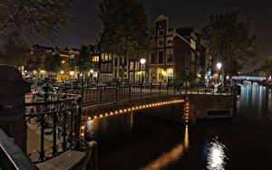Картинка Нидерланды Амстердам Здания Мост Водный канал Ночь Уличные фонари Велосипеды Города