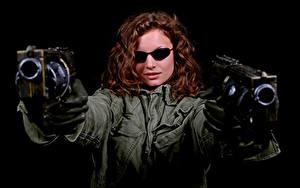 Фотографии Пистолет На черном фоне Шатенка Очков Куртках Руки Перчатки молодая женщина