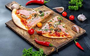 Фото Пицца Острый перец чили Томаты Чеснок Ветчина Разделочной доске Часть Пища Еда