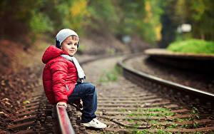 Фотографии Железные дороги Мальчишка Куртка В шапке Рельсы Сидя ребёнок