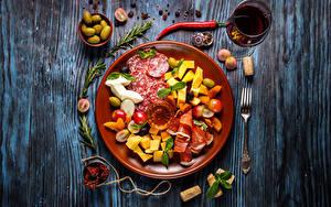 Фотография Колбаса Оливки Ветчина Сыры Вино Доски Тарелке Бокал Вилки Продукты питания