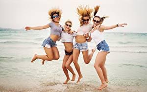 Фотография Море Пляжи Счастливый Отдых Очки Прыгать Четыре 4 Шорт Ноги молодые женщины