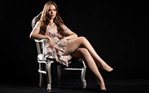 Фотография Silvy Sirius Стул Стулья Сидит Ноги Смотрят На черном фоне Молодые женщины