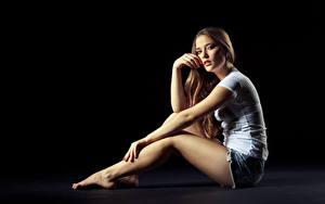 Фотография Сидящие Поза Шорты Рука Ноги Черный фон молодая женщина