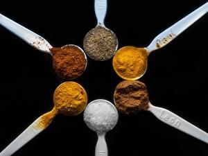 Картинки Приправы Вблизи Черный фон Ложка Соль cinnamon, saffron Kurkuma, Cayenne papper Пища