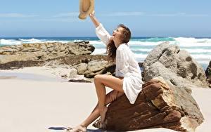 Фото Камни Море Лето Песок Сидит Ноги Шляпа Счастливые Релакс Шатенка девушка Природа
