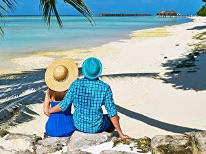 Обои для рабочего стола Камень Тропический Мужчина Курорты Пляже Объятие Две Шляпы Сидящие Вид сзади Природа Девушки