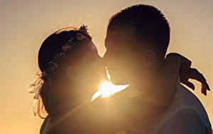 Картинка Рассвет и закат Мужчины Влюбленные пары Силуэты Две Поцелуй Обнимаются молодые женщины