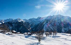 Обои Швейцария Горы Зимние Здания Альпы Снег Лучи света Braunwald